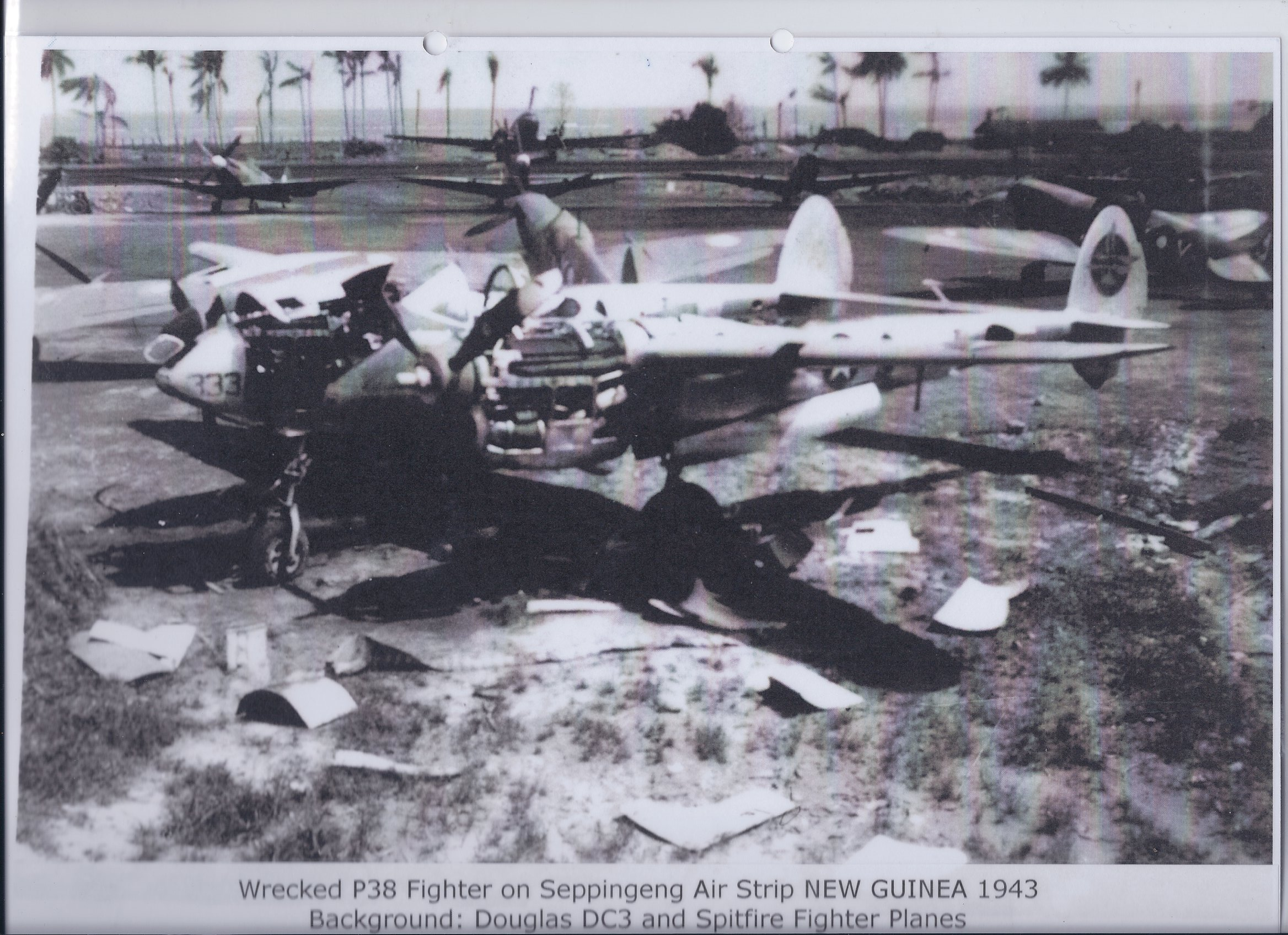 Wrecked P38 Fighter on Seppingeng Air Strip NEW GUINEA 1943. Background: Douglas DC3 and Spitfire Fighter Planes